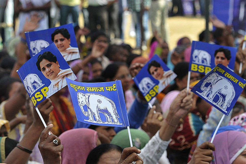 BSP supporters wave party flags at a political rally