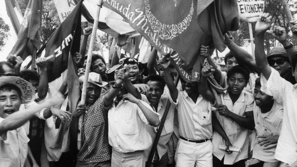 Young people holding flags with Arabic inscriptions