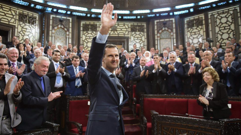 Bashar al-Assad waves to MPs on arrival at the Syrian parliament in Damascus (7 June 2016)