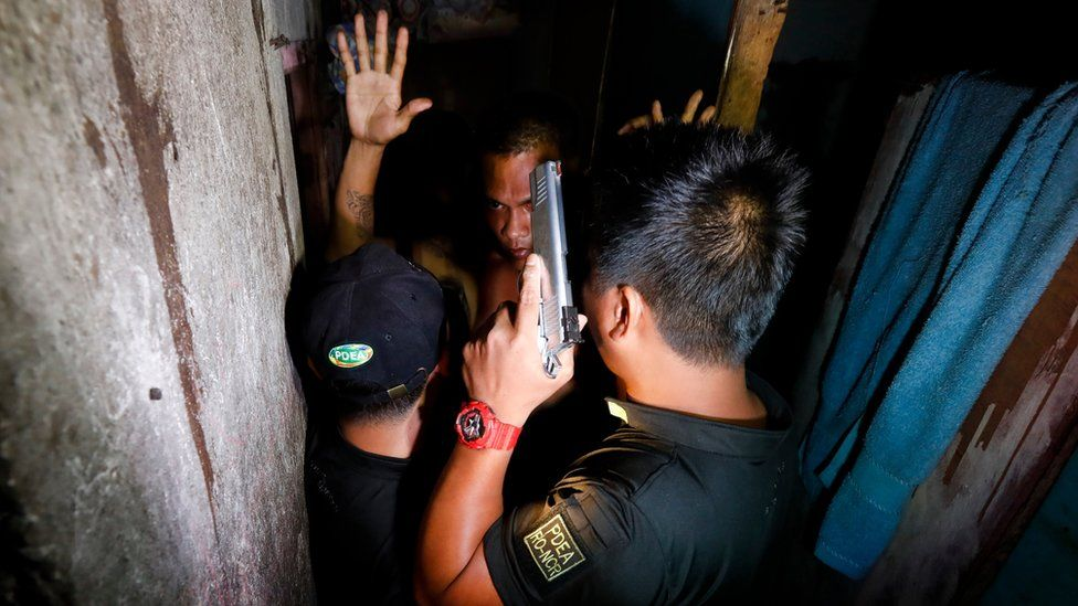 A Filipino who had exhibited suspicious behaviour raises his arms in front of operatives of the Philippine Drug Enforcement Agency (PDEA) during an anti-illegal drugs operation in Makati City, east of Manila, Philippines