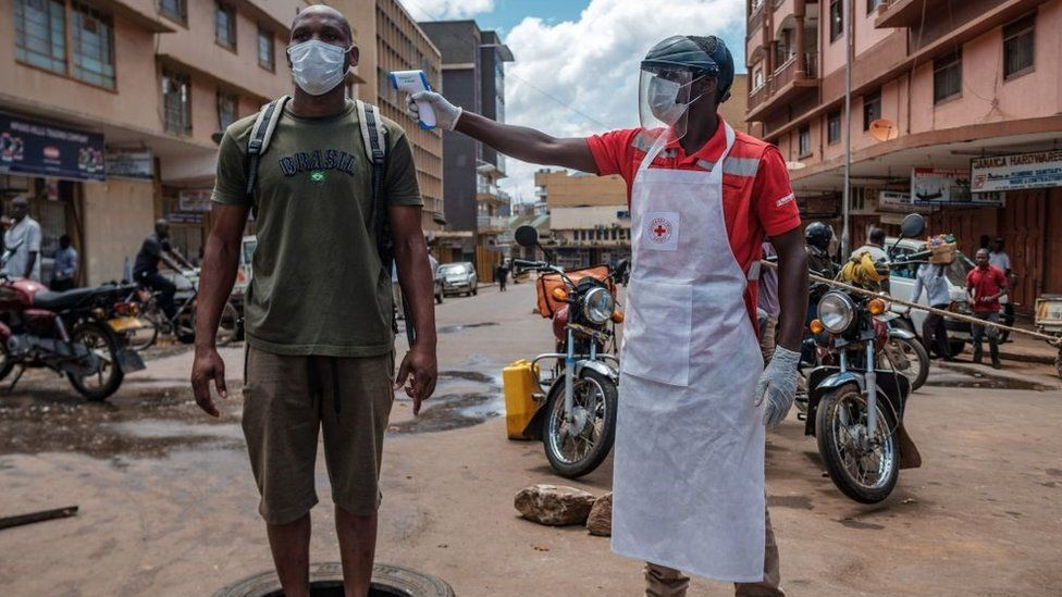 A Red Cross volunteer measures the temperature of a man before he can enter Nakasero market in Kampala, on April 1, 2020
