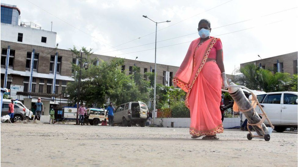 A woman carries an oxygen cylinder at Nalanda Medical College and Hospital campus on July 22, 2020 in Patna, India