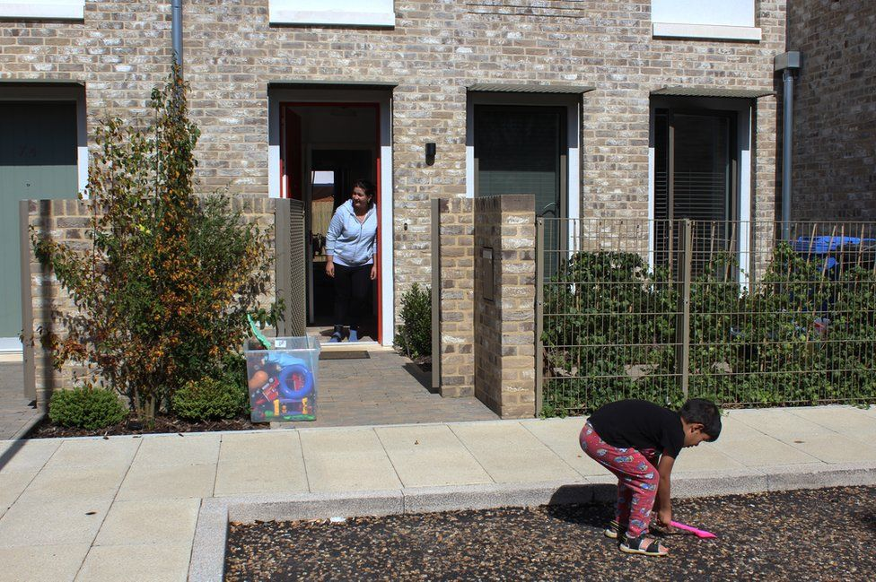 A mother watches as her son plays in the front garden