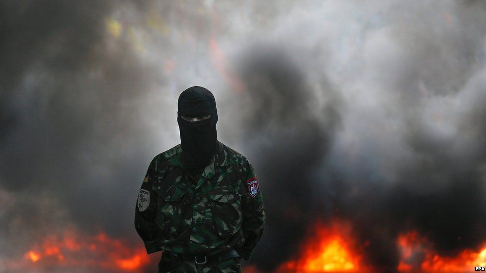 One of the members and supporters of Right Sector and other ultra-right political parties stands in front of burning tires during their protest on Grushevskogo street in Kiev, Ukraine, 3 July 2015