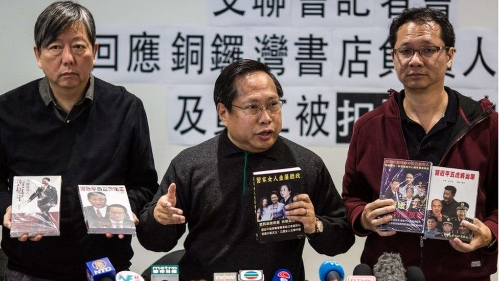 Pro-democracy group members Lee Cheuk Yan (2nd L), Albert Ho (C) and Richard Tsoi (4th L) hold up books during a press conference over the disappearance of five publishers in Hong Kong on January 3, 2016,