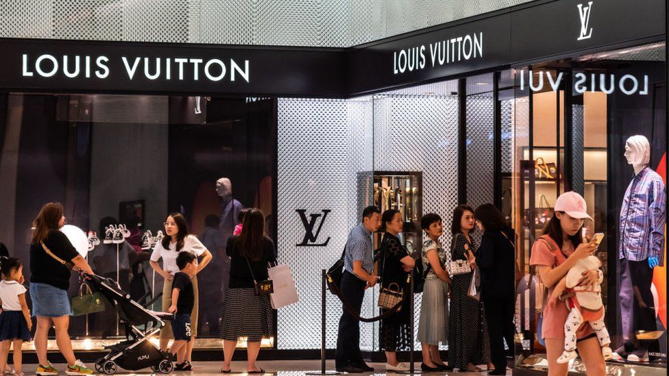 People queue up outside the Louis Vuitton store at a mall in Shenzhen, China