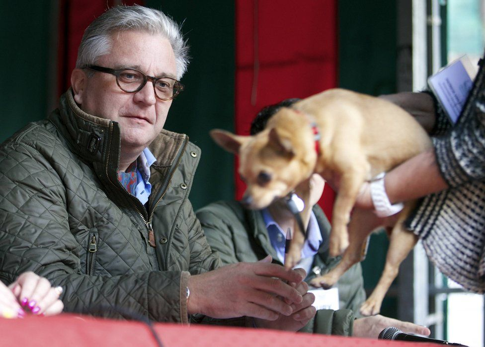 Prince Laurent of Belgium is presented with a small dog while judging a dog show in 2014