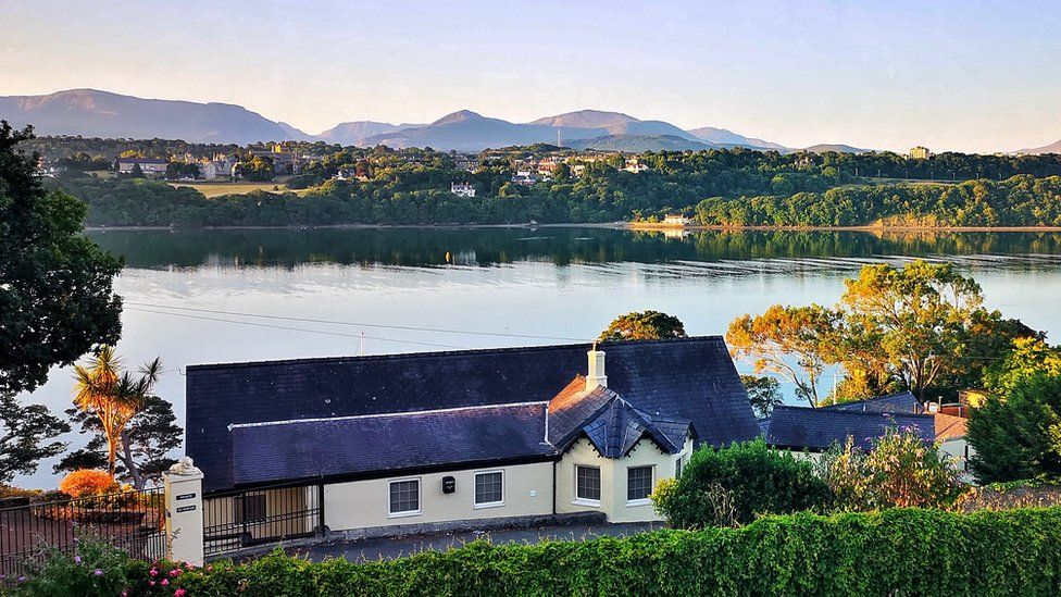 Warm sunshine glow over Menai Strait looking over roof tops and the mountains beyond