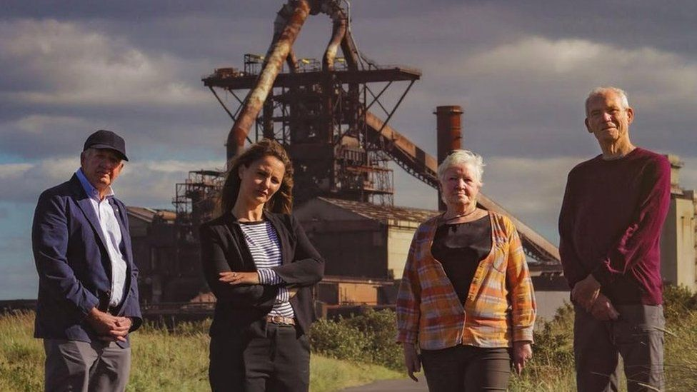 Four members of the Save our Steel Heritage group standing in front of the blast furnace