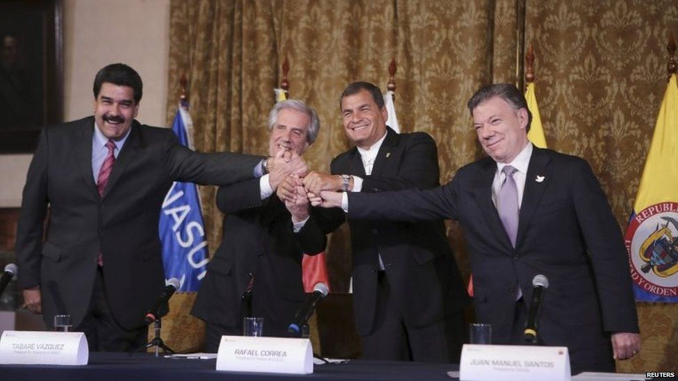 Venezuela's President Nicolas Maduro, Uruguay's President Tabare Vazquez, Ecuador's President Rafael Correa and Colombia's President Juan Santos hold hands after their meeting at the Carondelet Palace, in Quito, on 21 September, 2015.