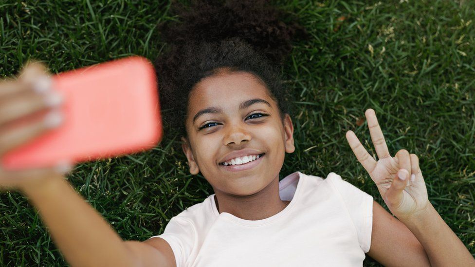 young girl takes selfie on smart phone