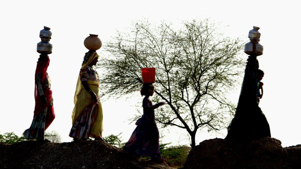 Women walking in line with water pots on their head