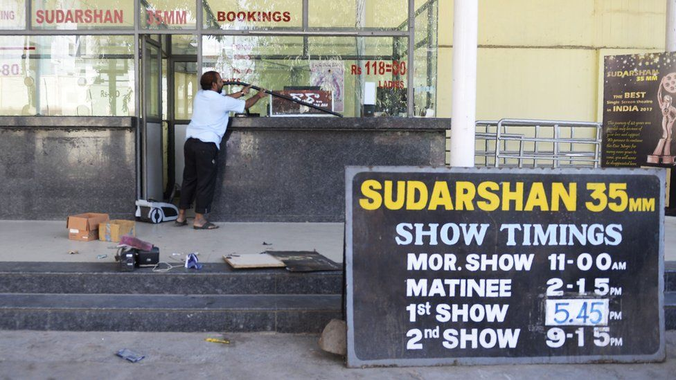 An Indian worker cleans a booking counter at a cinema theatre in Hyderabad on March 2, 2018.