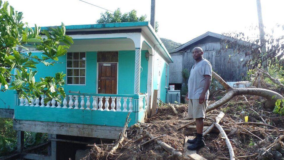 Matthew Durand stands next to a home in Petite Savanne