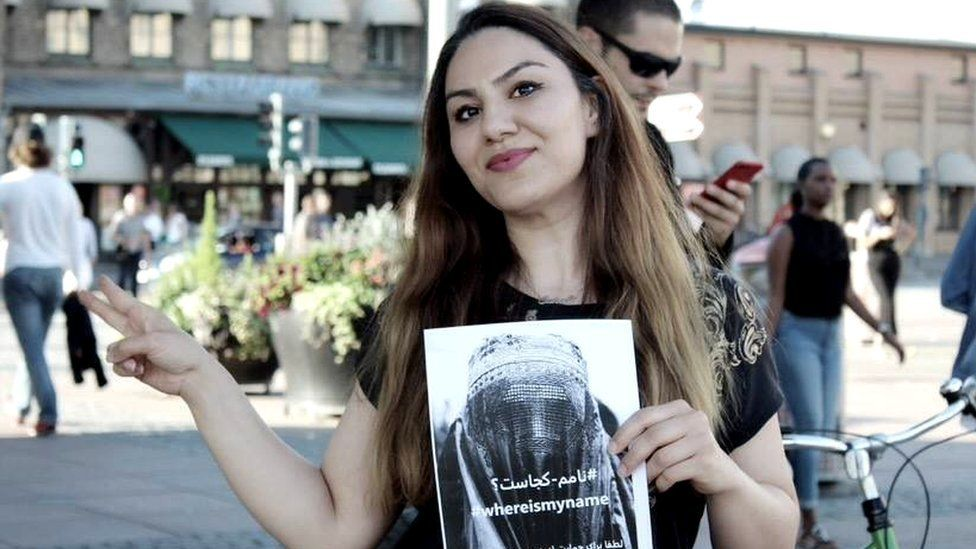 Sahar Samet holding a poster promoting the WhereIsMyName? campaign