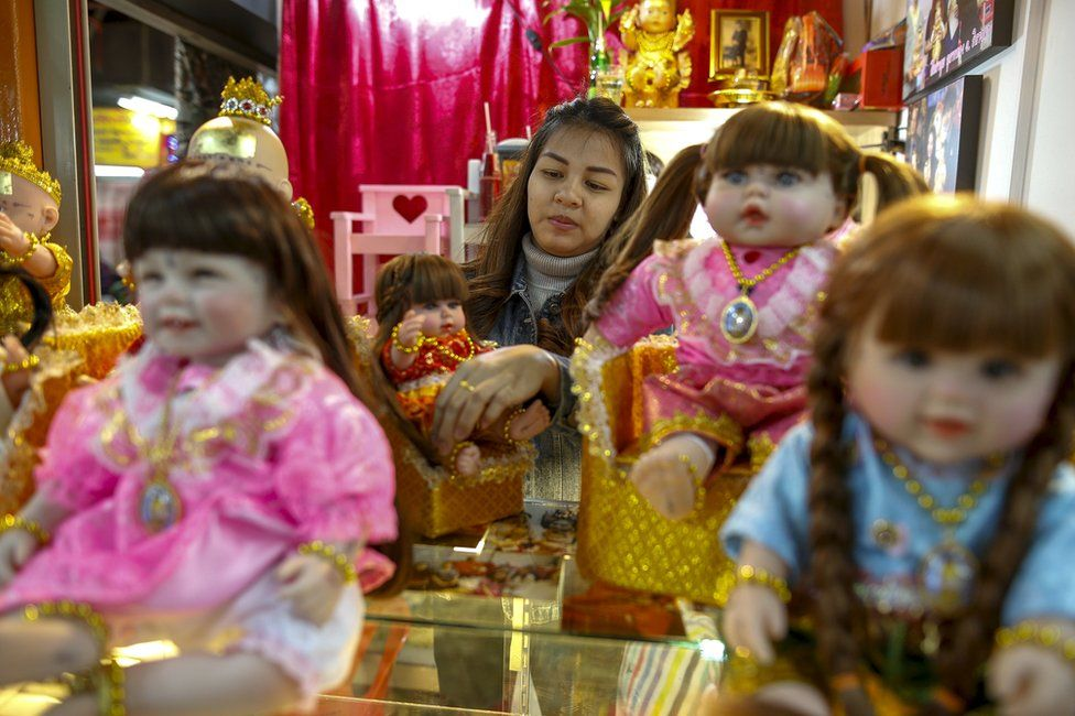 """A """"child angel"""" doll owner, Supattar Wichainan, 27, decorates her """"child angel"""" dolls at her shop inside a department store in Bangkok, Thailand, 26 January 2016"""