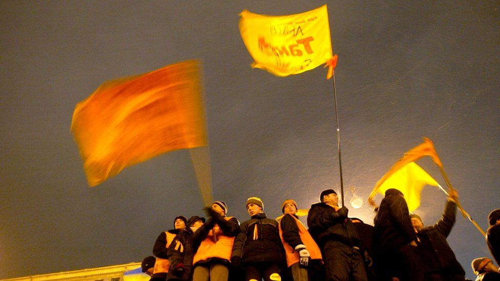 Supporters of Viktor Yushchenko wave flags during a November 2004 rally in Kiev
