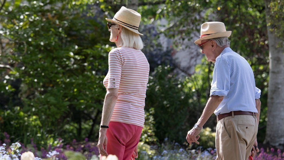 An elderly couple walking through Regent's Park on a warm, sunny afternoon on May 09, 2020 in London, United Kingdom.