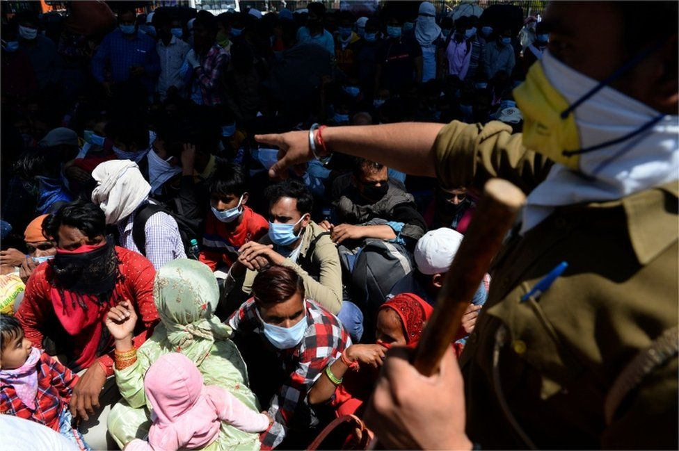 A police officer instructs migrant workers and their family members to line-up as they leave India's capital for their homes during a government-imposed nationwide lockdown as a preventive measure against the COVID-19 coronavirus