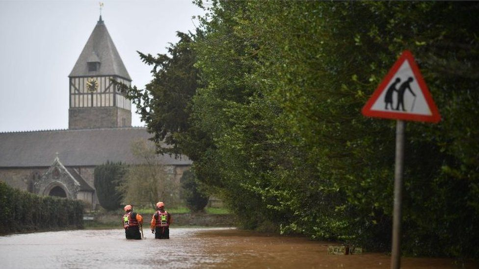 Hereford Fire and Rescue personnel check the depth of flood water as they go along a flooded road in the village of Hampton Bishop in Herefordshire