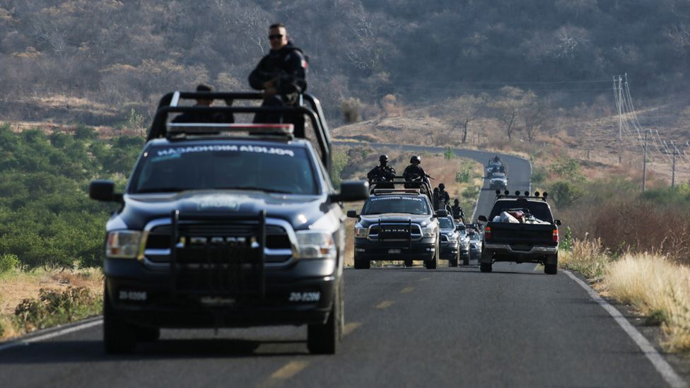 A State police convoy patrols a road in El Aguaje after a visit of Vatican's ambassador to Mexico Franco Coppola to the area and to the municipality of Aguililla, an area where the Jalisco New Generation Cartel (CJNG) and local drug gangs are fighting to control the territory, in Michoacan state, Mexico April 23, 2021.
