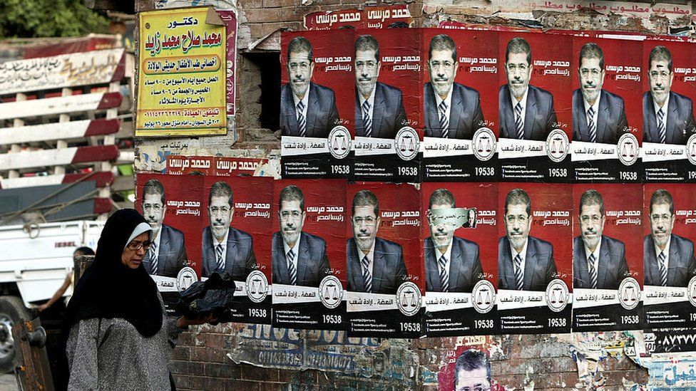 An Egyptian woman walks past election campaign posters for the Muslim Brotherhood's presidential candidate, Mohammed Morsi, in Cairo (21 May 2012)