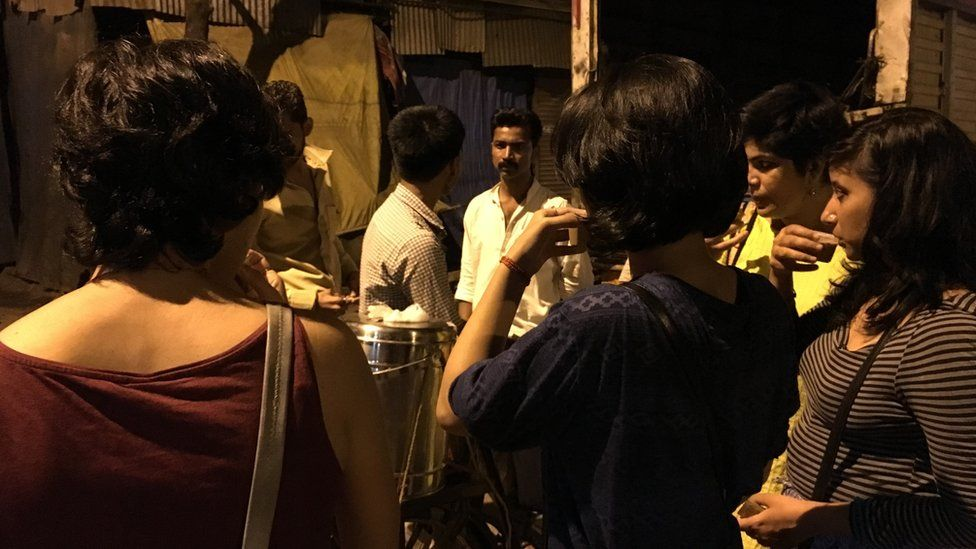 Women having a cup of tea on the side of the road in Mumbai after midnight