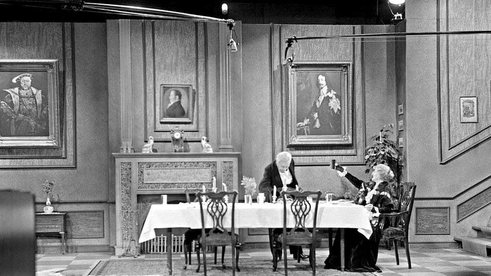A wide shot of the Dinner for One production is seen here, with boom mics extending from the sides and the set dressing clearly visible.