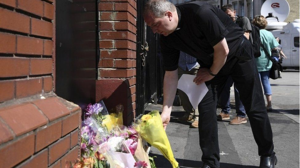 A priest leaves flowers at the scene of a terror attack in Finsbury Park