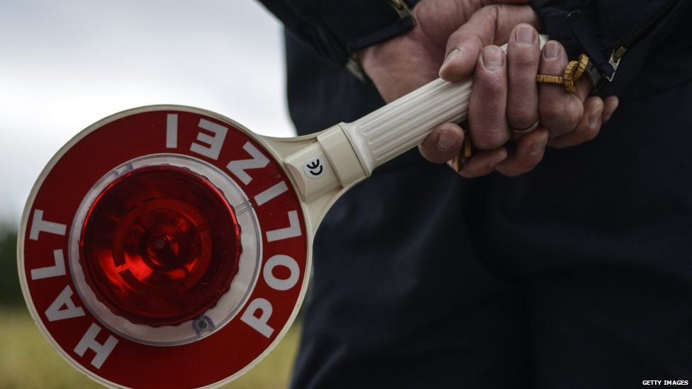 A German police officer holds a stop sign as he observes traffic