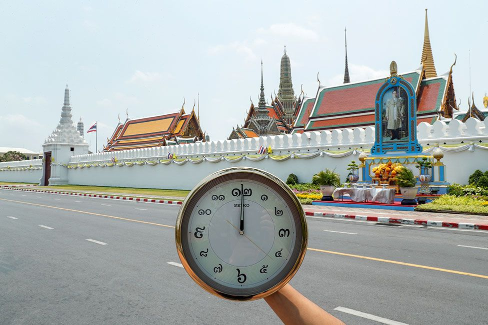 A clock showing the time at noon at Wat Phra Si Rattana Satsadaram (The Temple of the Emerald Buddha, also known as The Grand Palace) in Bangkok, Thailand