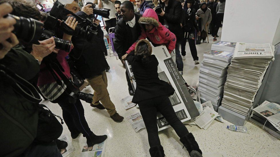 People fighting over a television