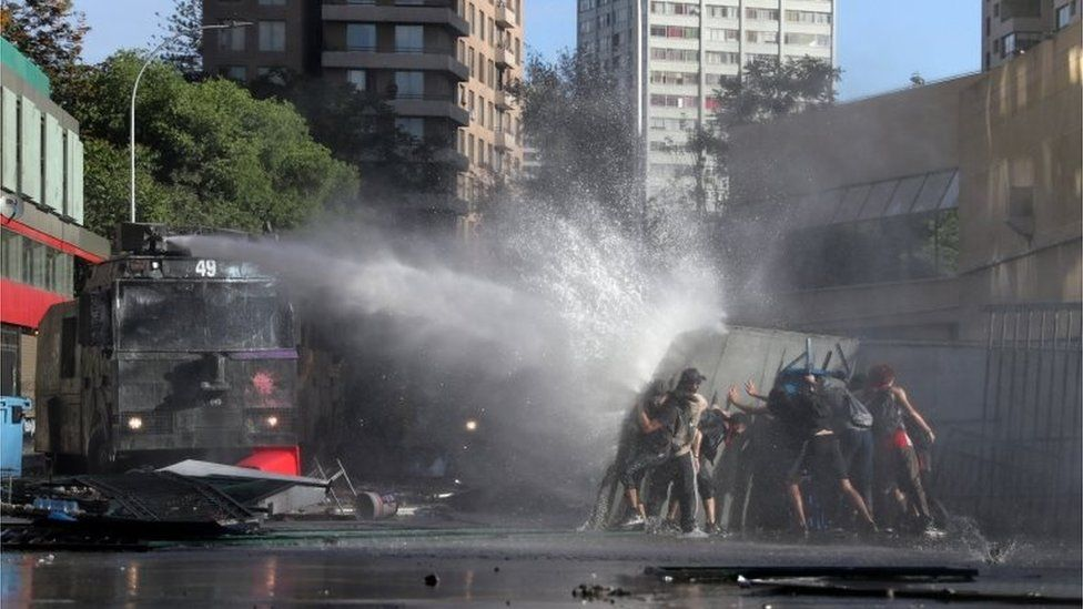 A riot police water cannon sprays water towards demonstrators during a protest in Santiago.