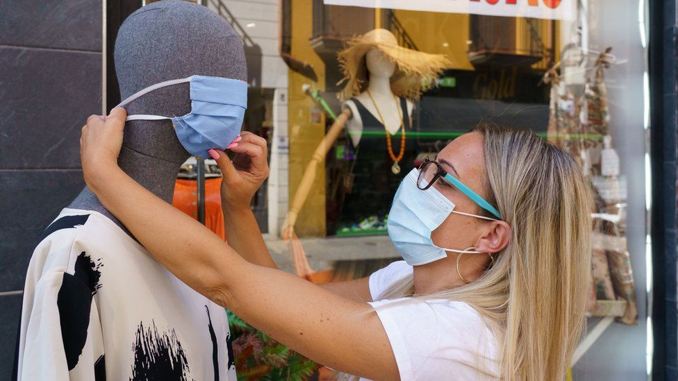 A woman places a mask on a mannequin outside a clothing store in Aranda de Duero, near Burgos on 7 August