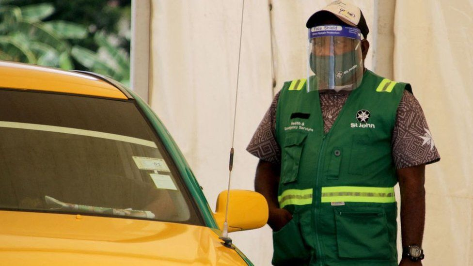 A health worker stands by as people arrive in cars for a covid-19 test