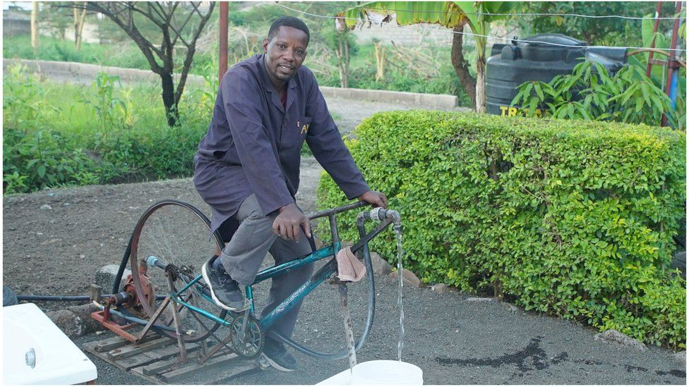 Bernard Kiwia outside on a bicycle which runs a water-pump