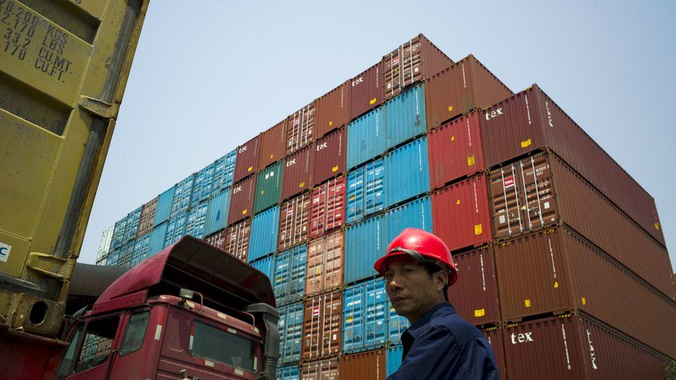 A worker stands in front of shipping containers