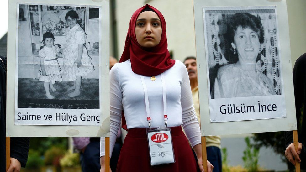 A woman holds pictures of victims during a silent remembrance commemorating the 25th anniversary of an arson attack killing two Turkish women and three girls by right-wing extremists in Solingen