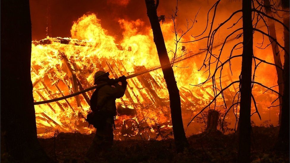 A Cal Fire firefighter sprays water on a home next to a burning home as the Camp Fire moves through the area