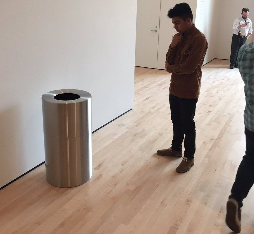 A man staring at a bin