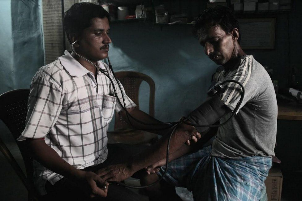 Sanjoy Mondal checking blood pressure level of a patient