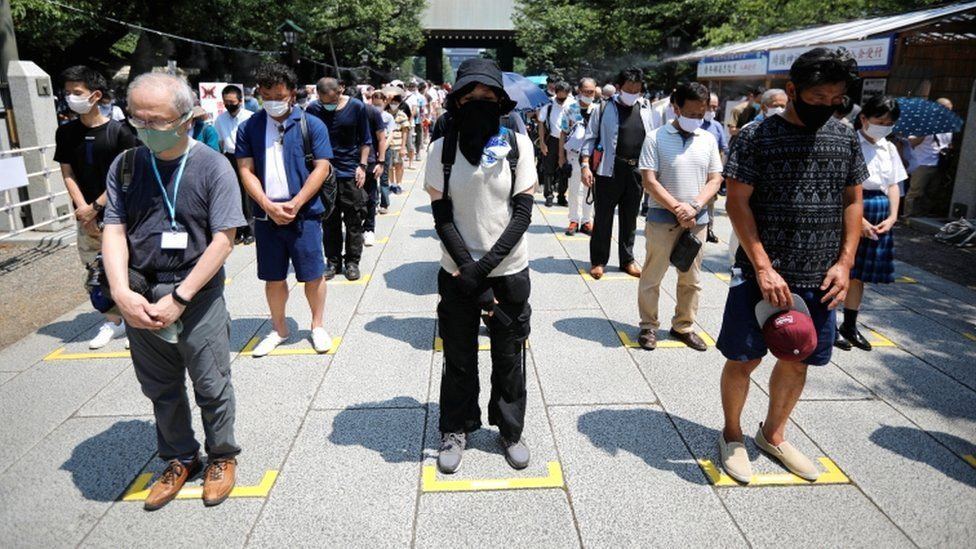 People practice social distancing while paying a silent tribute during their visit to Yasukuni Shrine