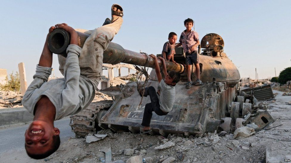 Syrian children play on a destroyed tank in south of Kobane in Syria, 22 June 2015.