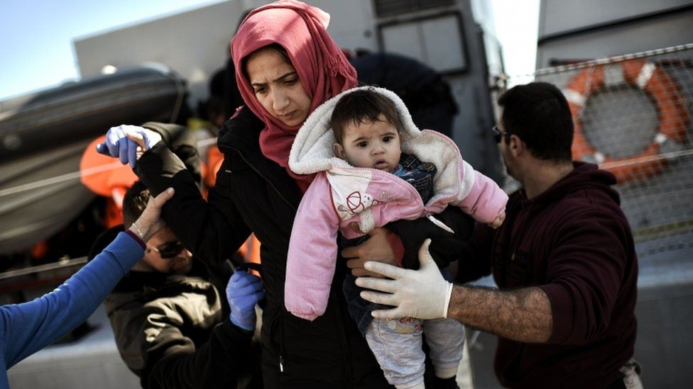 A woman holding a baby is assisted as refugees and migrants disembark from an open sea ship of the Greek coast guard in Mytilene, the port of the northern island of Lesbos, on February 22, 2016, after crossing the Aegean sea from Turkey