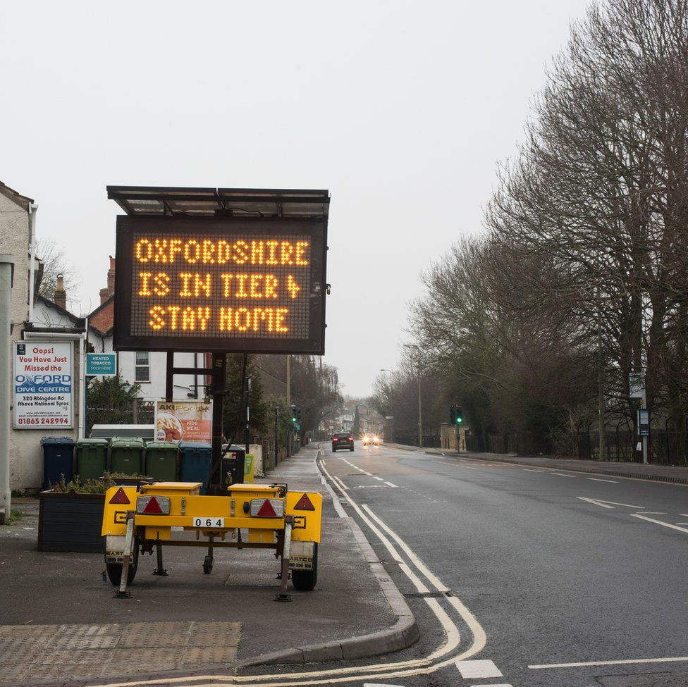 An image of a sign instructing people to stay at home next to a main road