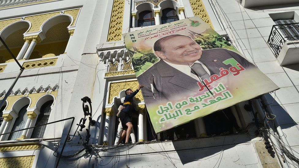 Algerian demonstrators tear down a large billboard with a picture of former President Abdelaziz Bouteflika.