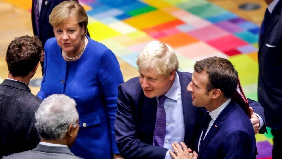 British Prime Minister Boris Johnson (2nd R) salutes French President Emmanuel Macron (R) upon their arrival for a round table meeting as part of a European Union summit at European Union Headquarters in Brussels on October 17, 2019