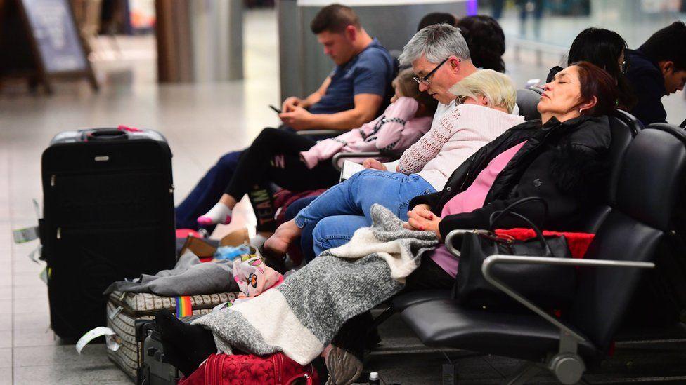 Passengers sleep in the terminal