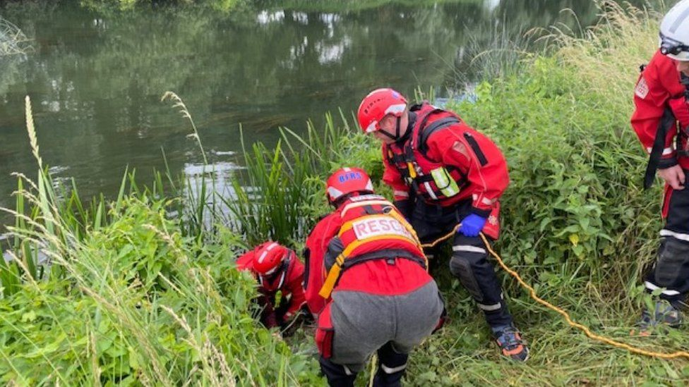 Woman being rescued from river