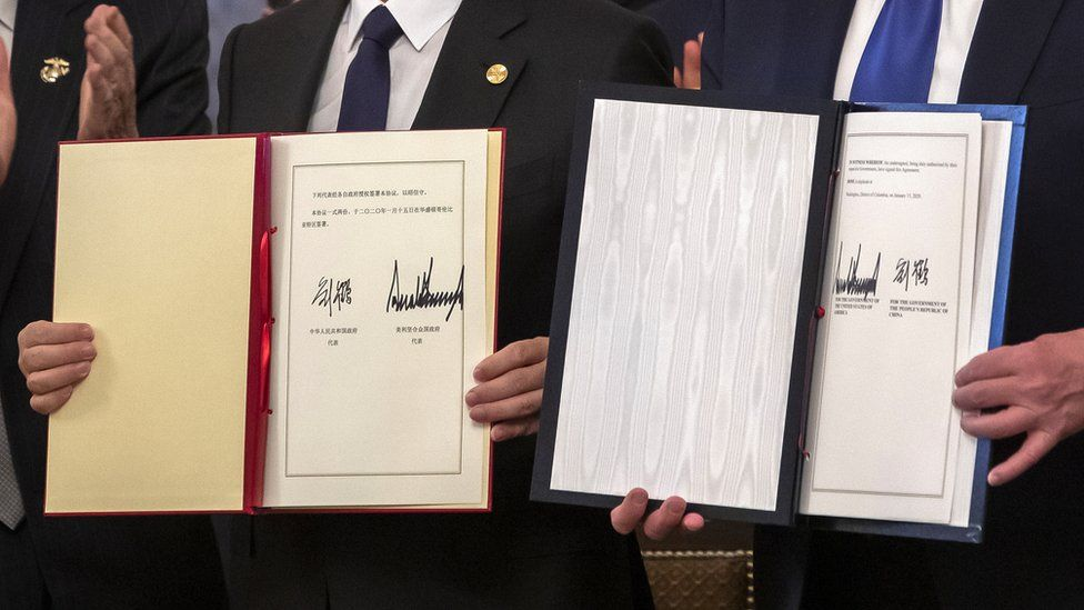 Chinese vice premier Liu He (L) and US president Donald J. Trump (R) sign a partial trade deal